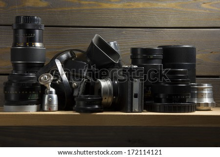 Wooden shelf in the larder with the old photographic equipment - lenses and cameras - outdated but still applicable.