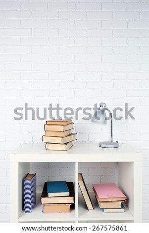 Wooden shelf with books and lamp on brick wall background - stock photo