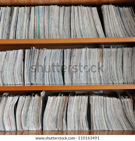 wooden shelf with brochures and piles of paper - stock photo
