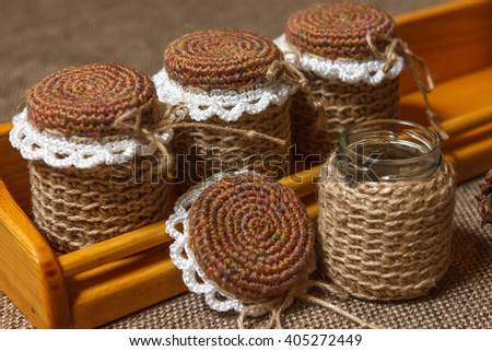 Wooden shelves and multicolored crochet handmade jars of spices - stock photo