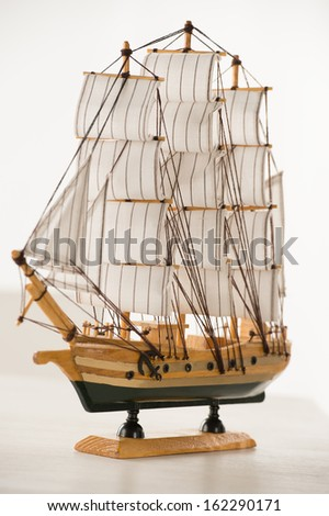 Wooden ship toy model on white table against white background - stock photo