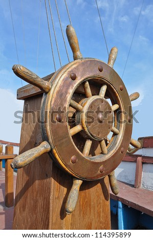 wooden ship wheel on a blue background - stock photo
