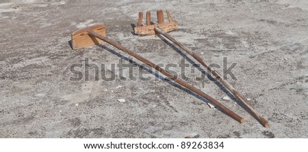 Wooden shovel and rake on the ground - stock photo