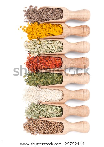 Wooden shovels with different spices scattered from them on white background - stock photo