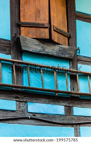 Wooden shutter and ladder on turquoise half timbered building wall.