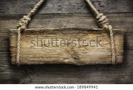 Wooden sign hanging on a rope on wooden background  - stock photo