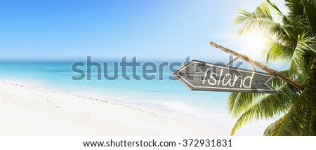 Wooden sign Island on tropical white sand beach summer background. Lush tropical foliage and sunshine. Blue ocean at perfect day. No people. - stock photo
