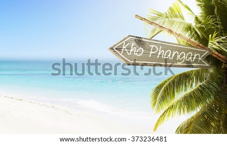 Wooden sign Kho Phangan on tropical white sand beach summer background. Lush tropical foliage and sunshine. Blue ocean at perfect day. No people.  - stock photo