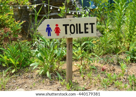 Wooden sign pointing way in garden to restrooms or toilets - stock photo