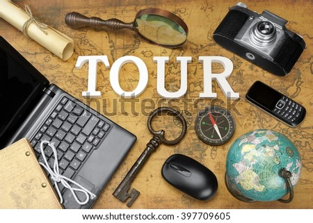 Wooden Sign Tour, Laptop, Vintage 35mm Photo Camera, Retro Key,  Globe, Magnifier, Compass, GSM Phone, Computer Mouse And Letter On The Old Map, Flat Lay, Top View - stock photo