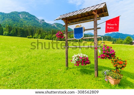 "Wooden sign ""Welcome to Austria"" on green meadow in Alps Mountains, Weissensee lake, Austria - stock photo"