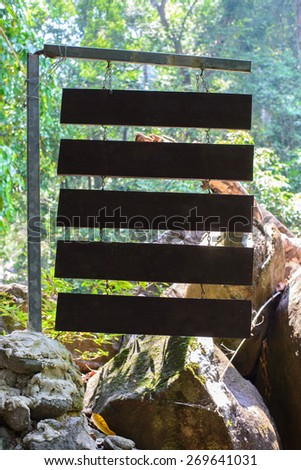 wooden sign with forest background - stock photo