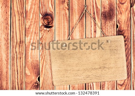 Wooden signboard with rope hanging on wood planks background - stock photo