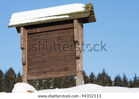 Wooden signpost in the snow in front of a blue sky