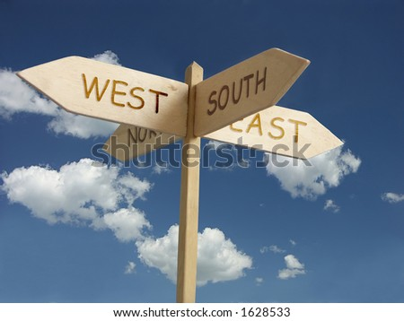 Wooden signpost indicating four quarters of the world - stock photo