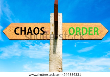 Wooden signpost with two opposite arrows over clear blue sky, Chaos versus Order messages - stock photo