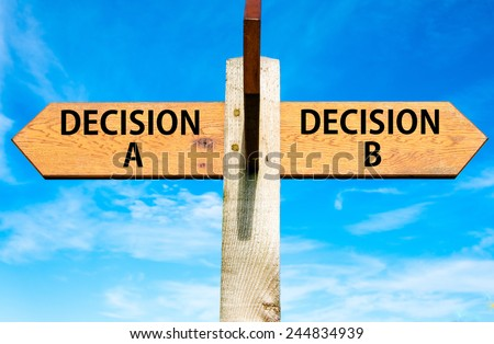 Wooden signpost with two opposite arrows over clear blue sky, Decision A and Decision B messages, Right choice conceptual image - stock photo
