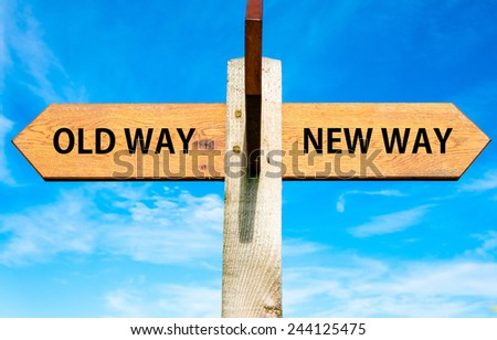 Wooden signpost with two opposite arrows over clear blue sky, Old Way and New Way signs - stock photo