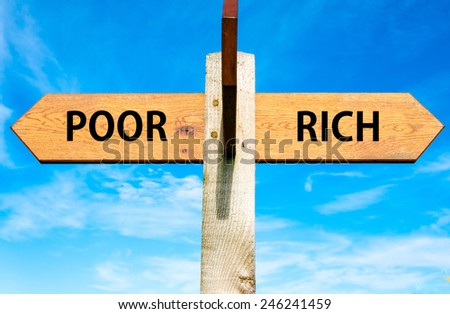 Wooden signpost with two opposite arrows over clear blue sky, Poor versus Rich messages - stock photo