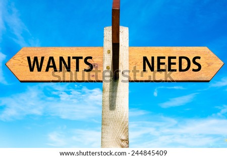 Wooden signpost with two opposite arrows over clear blue sky, Wants versus Needs messages, Consumerism conceptual image - stock photo