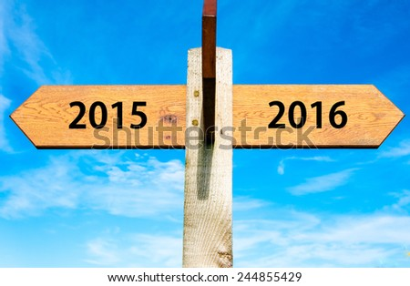 Wooden signpost with two opposite arrows over clear blue sky, year 2015 and 2016 signs, Happy New Year conceptual image - stock photo