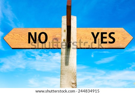 Wooden signpost with two opposite arrows over clear blue sky, YES and No messages, Decisional conceptual image - stock photo
