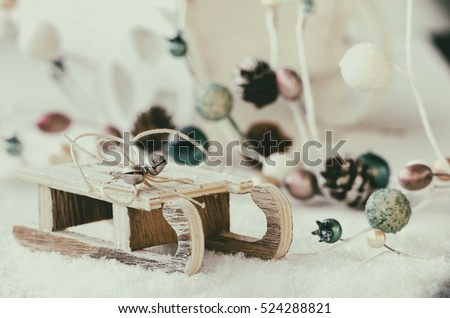 Wooden sled with snow, Christmas garland and cart