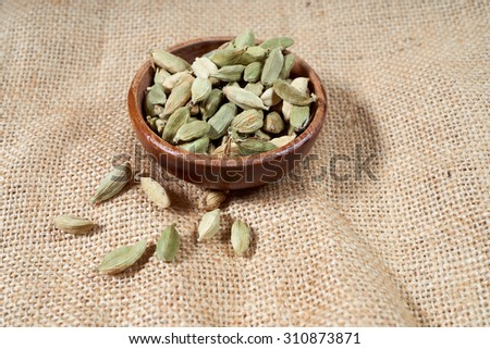 Wooden small bowl with whole green cardamom seeds