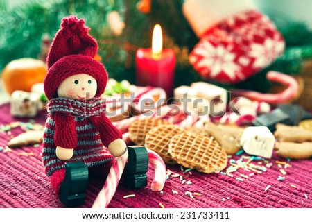 Wooden smiling doll with sweet striped candy canes on christmas background. New-year's indoor still-life. Close-up. - stock photo