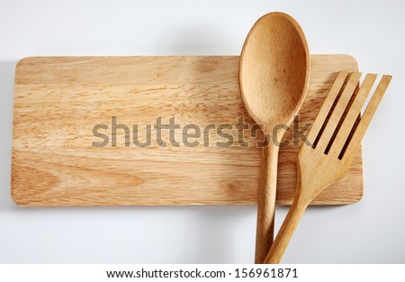 Wooden spatula and spoon  on the chopping board - stock photo