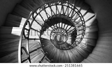 Wooden spiral stairs with rails in sun light interior black and white art - stock photo
