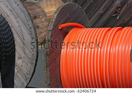 wooden spool with black and orange cables - stock photo