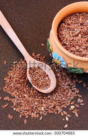Wooden spoon and ceramic bowl with flax seeds on a metal background - stock photo