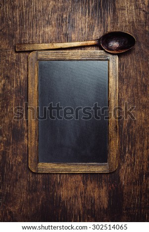 Wooden spoon and chalkboard on a rustic dark background - stock photo