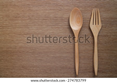 Wooden spoon and fork on table background