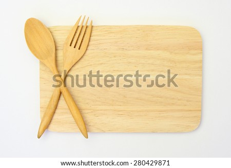 wooden spoon and fork on wooden board against white background - stock photo