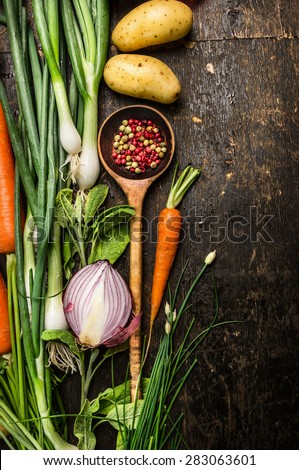 Wooden spoon and fresh vegetables ingredients for cooking on dark background, top view, place for text - stock photo