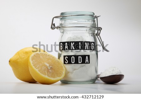 wooden spoon and jar of baking soda with lemon - stock photo