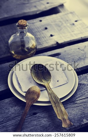 Wooden spoon, bottle with olive oil and white ceramic plates on old wooden table background, Table serving - stock photo