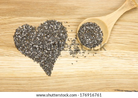 wooden spoon filled with black chia seeds and heart symbol - stock photo