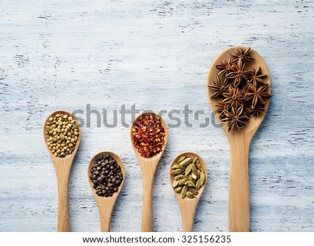 Wooden spoon filled with herbs and spices on white painted table - stock photo