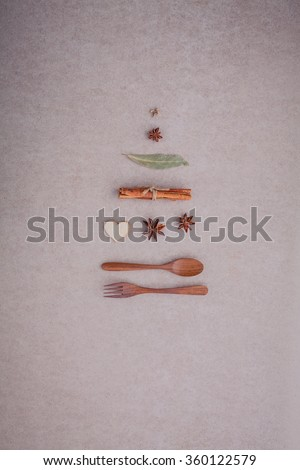 Wooden spoon ,fork ,cinnamon ,star anise ,wooden heart and bay leaves set up on brown paper board concept for Sweet menu and Christmas Day - stock photo