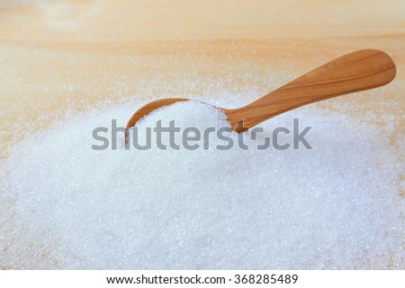 Wooden spoon in a pile of white sugar - stock photo