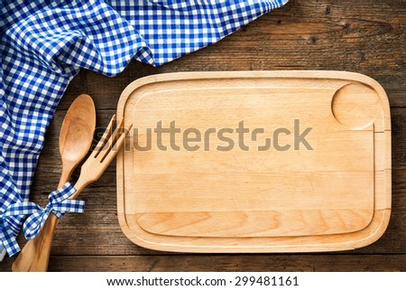 Wooden spoon on a cutting board with a blue checkered tablecloth - stock photo