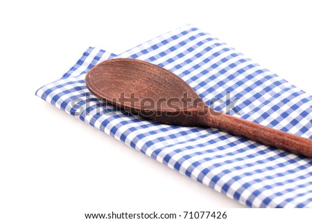 wooden spoon on checkered dishtowel isolated on white background - stock photo