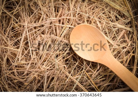 wooden spoon on hay box background - stock photo