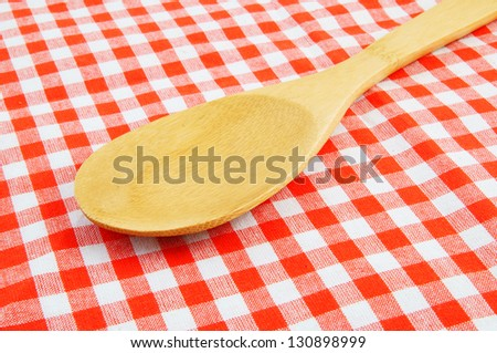 Wooden spoon on red checked tablecloth
