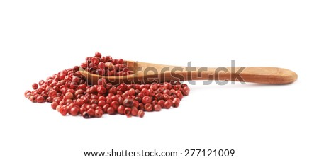 Wooden spoon over the pile of the red pepper seeds isolated over the white background - stock photo