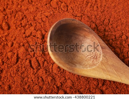 Wooden spoon over the surface coated with the red powdered paprika as a backdrop composition - stock photo