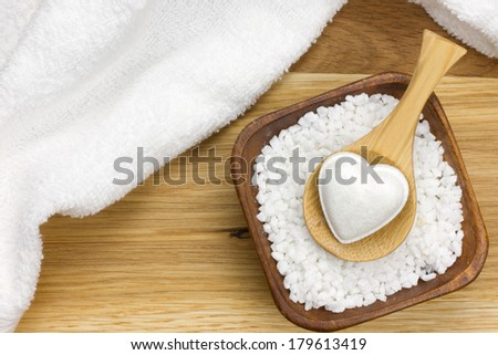 wooden spoon with bath fizzer in heart shape on bowl filled with bath salt and white towel next to it - stock photo